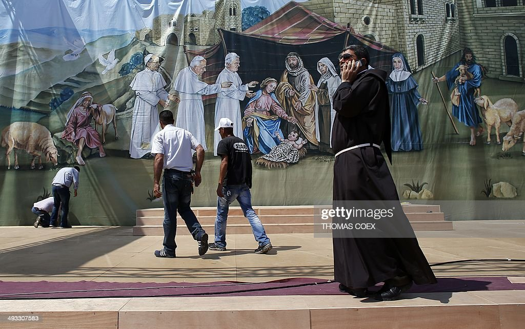 People, one being a Franciscan priest (C), stand in front of a giant banner featuring Jesus' birth with former Popes (LtoR) Paul VI, Jean-Paul II, and Benedict XVI visiting him, on May 23, 2014 at Manger Square outside the church of Nativity -revered as the site of Jesus' birth- in the West Bank city of Bethlehem.