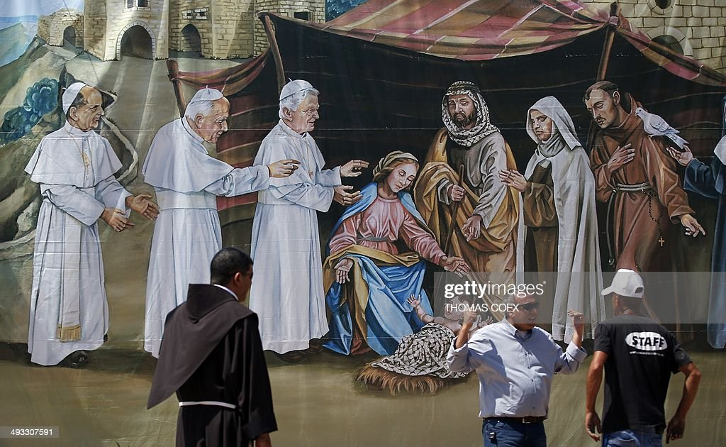 People, one being a Franciscan priest (L), stand in front of a giant painting featuring Jesus' birth with former Popes (LtoR) Paul VI, Jean-Paul II, and Benedict XVI visiting him, on May 23, 2014 at Manger Square outside the church of Nativity in the West Bank city of Bethlehem.