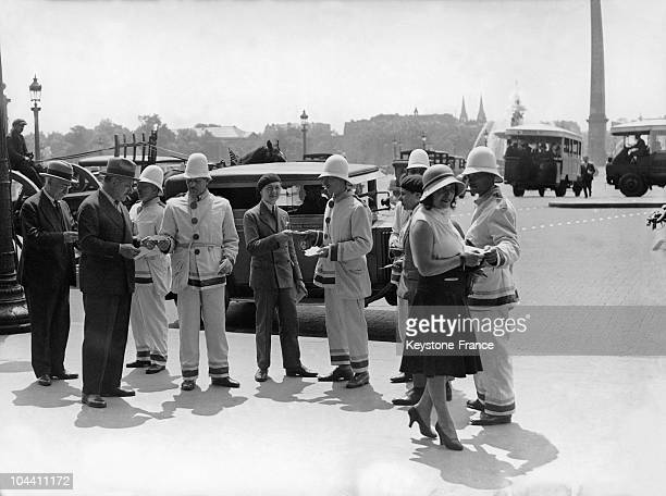 People originating from French colonies hand out pamphlets on the Place de la Concorde for the opening of the Colonial Exhibition taking place from...