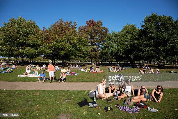 People out enjoying the unseasonally hot weather as a summertime heat wave hits London and the UK in what should be Autumn Summer prolonged in a...