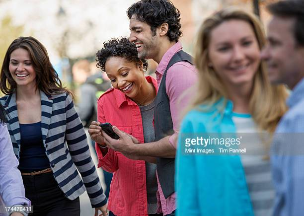 People outdoors in the city in spring time. A group of men and women, two looking at a cell phone screen and laughing.