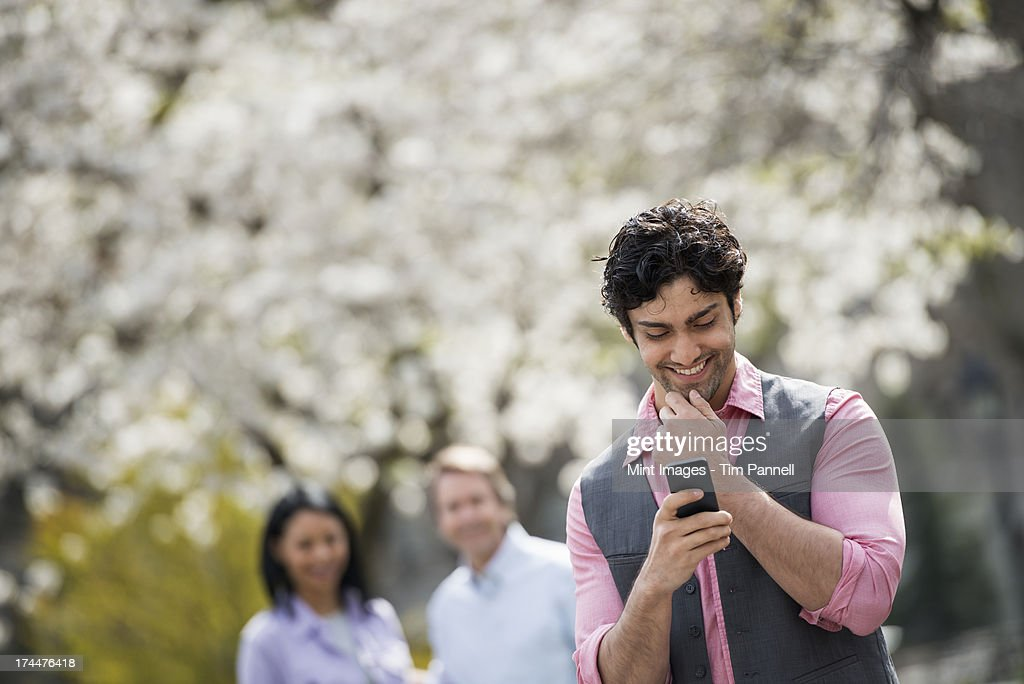 People outdoors in the city in spring time. Cherry blossom on the trees. A man checking his cell phone, and two people behind him.