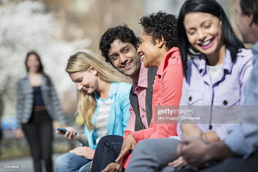 People outdoors in the city in spring time. Five people sitting in a row, one looking at a mobile phone. A woman approaching in the distance.