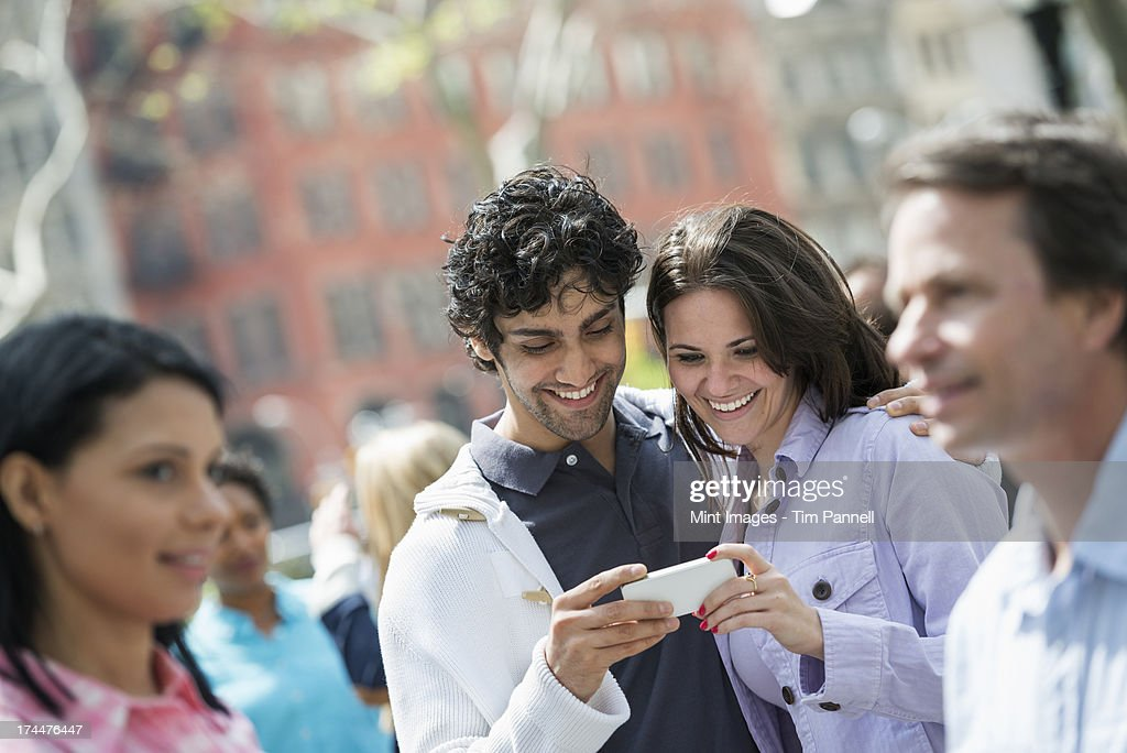 People outdoors in the city in spring time. New York City. A group of men and women, a couple at the centre looking at a cell phone.