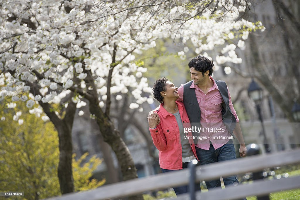 People outdoors in the city in spring time. New York City park. A couple, man and woman looking into each others eyes.