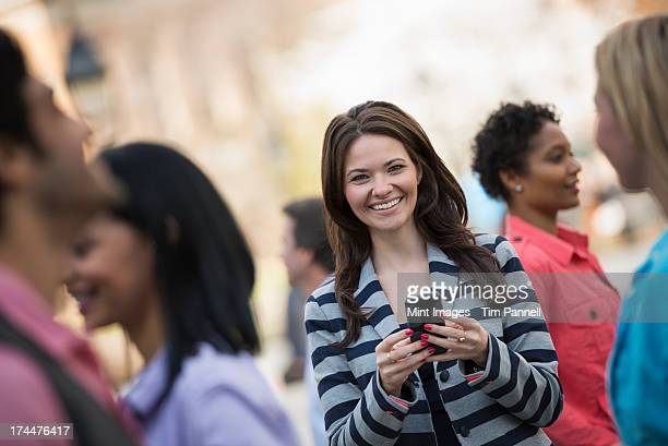 People outdoors in the city in spring time. New York City park. A young woman holding a mobile phone, and looking up at the camera.
