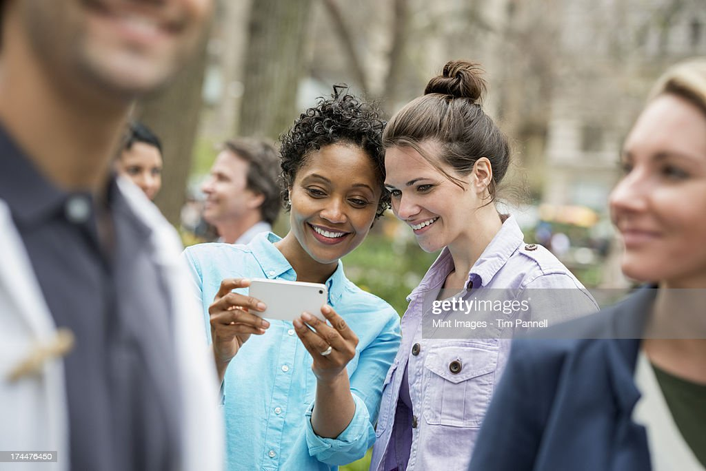 People outdoors in the city in spring time. New York City park. Two women in a group of friends, looking at a cell phone and smiling.