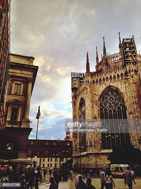 People Outside Milan Cathedral Against Cloudy Sky