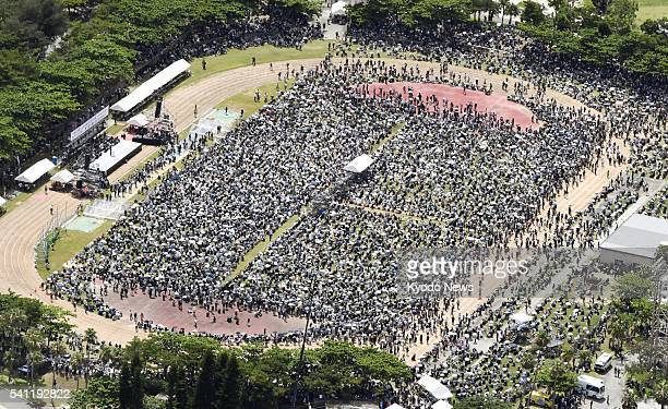 People pack a park in Naha in Japan's southernmost island prefecture of Okinawa on June 19 during a rally to voice their anger about crimes committed...