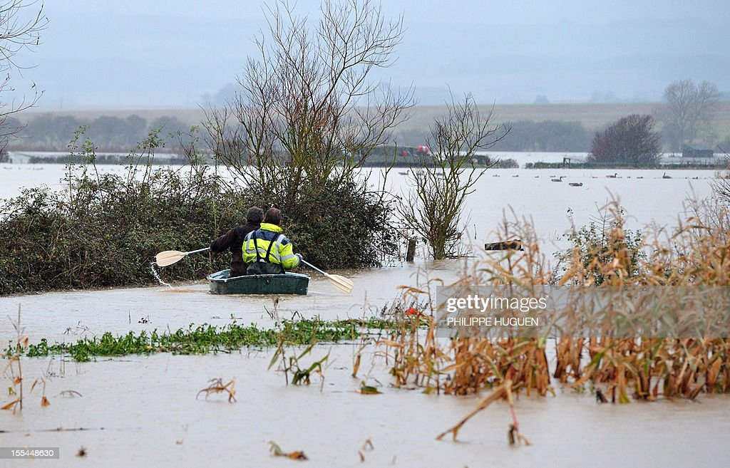 People paddle in a small boat on a flooded corn field, on November 4, 2012, in Marquise, northern France, following heavy rains in the region.