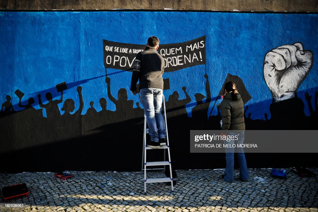 People paint a mural reading 'Damn theTroika! The power lies in the People' in Lisbon on February 24, 2013. The mural by the movement 'Damn the Troika' calls for participation in a protest against government's austerity measures in Lisbon on March 2.