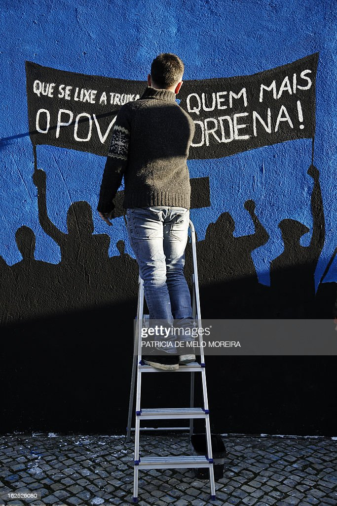 People paint a mural reading 'Damn theTroika! The power lies in the People' in Lisbon on February 24, 2013. The mural by the 'Damn the Troika' movement calls for participation in a protest against government's austerity measures in Lisbon on March 2.