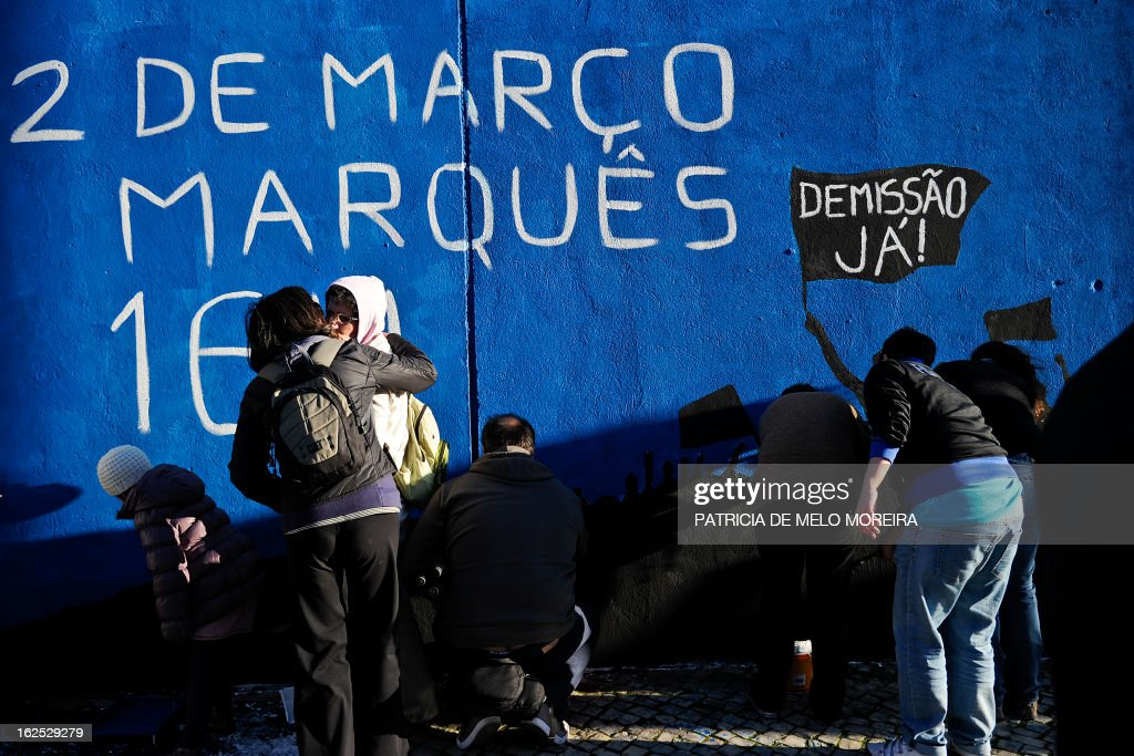 People paint part of a mural reading 'March 2, Marques, 16h. Resignation Now!'' in Lisbon on February 24, 2013. The mural by the movement 'Damn the Troika' calls for participation in a protest against government's austerity measures in Lisbon on March 2. AFP PHOTO / PATRICIA DE MELO MOREIRA