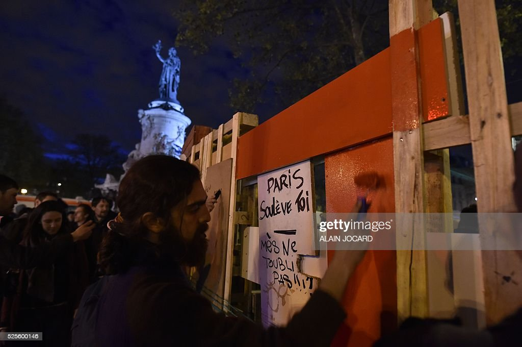 People paint slogans reading 'Paris, do revolt, but do not forget yourself !' on Place de la Republique during the Nuit Debout, or 'Up All Night' movement on April 28, 2016 in Paris. The 'Nuit Debout' demonstrations began on March 31 in opposition to the government's proposed labour reforms.