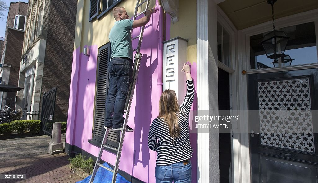 People paint the facade of a restaurant in pink, the colour of the Giro d'Italia cyling race, in Apeldoorn, on May 2, 2016. A The Giro d'Italia will start in Apeldoorn on May 6, 2016. / AFP / ANP / Jerry Lampen / Netherlands OUT