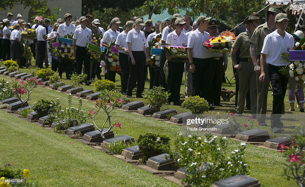 People parade carrying wreaths during the Wreath Laying Ceremony at the Kanchanaburi War Cemetery April 25, 2013 in Kanchanaburi, Thailand. Hellfire Pass is a small section of the Burma-Thailand railway which was built by POW's and Asian Laborers under horrific conditions during the Second World War (WWII). Heavy loss of life was suffered during construction due to disease, starvation and exhaustion.