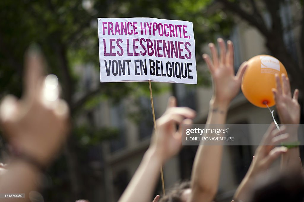 People parade during the homosexual, lesbian, bisexual and transgender (HLBT) visibility march, the Gay Pride, on June 29, 2013 in Paris, exactly one month after France celebrated its first gay marriage. Sign reads: 'Hyprocrite France, lesbians go to Belgium'.