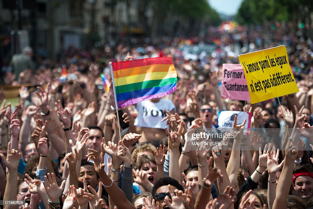 People parade during the homosexual, lesbian, bisexual and transgender (HLBT) visibility march, the Gay Pride, on June 29, 2013 in Paris, exactly one month to the day since France celebrated its first gay marriage. The board at right reads : 'Love among equals is not so different'.