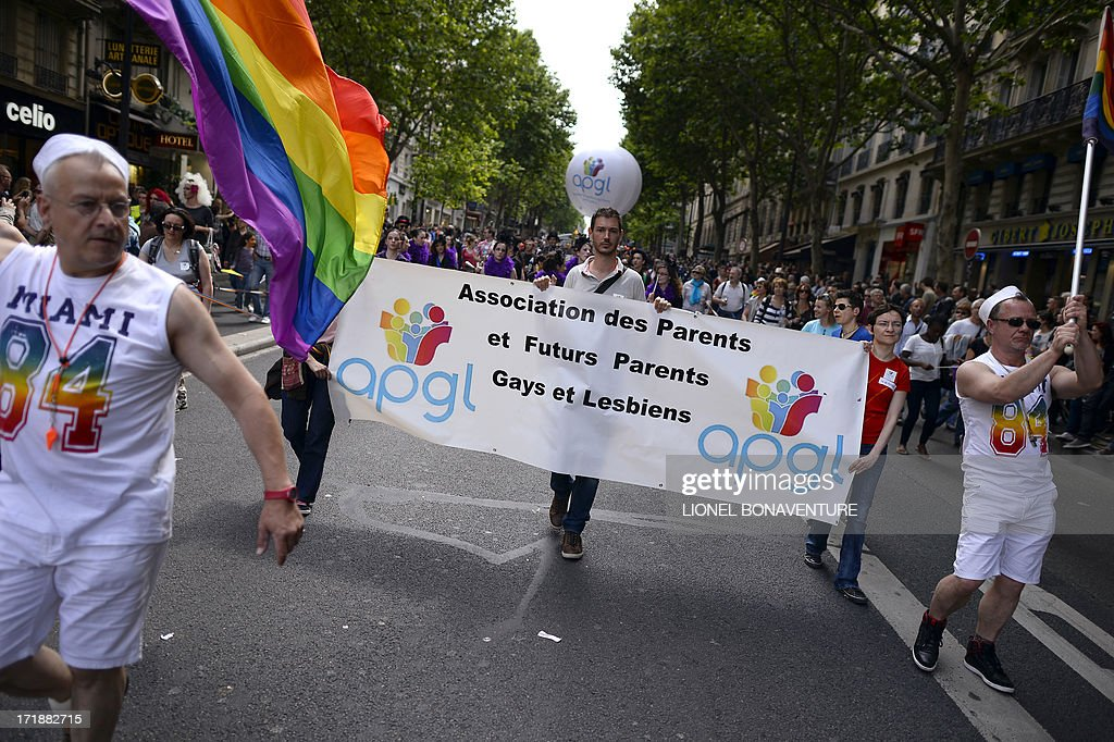 People parade during the homosexual, lesbian, bisexual and transgender (HLBT) visibility march, the Gay Pride, on June 29, 2013 in Paris, exactly one month after France celebrated its first gay marriage. Banner reads: 'Association of parents and futur gay and lesbian parents'.