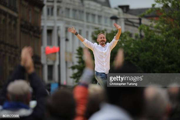 People parade on a 100m long catwalk installed high above the ground as part of What Is The City But The People show in Piccadilly Gardens on June 29...