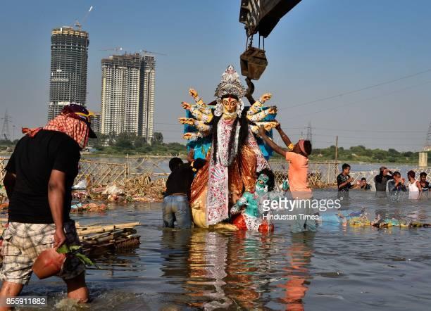People participate during a Durga idol immersion procession on Vijayadasami at Yamuna River at Kalindi Kunj on September 30 2017 in New Delhi India...