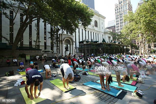 People participate in a free outdoor yoga class in Bryant Park on June 30 2009 in New York City After weeks of unseasonably wet weather New York and...