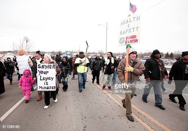People participate in a national milelong march to highlight the push for clean water in Flint February 19 2016 in Flint Michigan The march was...