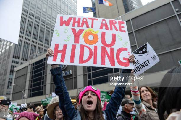 People participate in a Tax Day protest on April 15 2017 in New York City Activists in cities across the nation are marching today to call on...