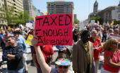 People participate in a Tea Party Protest in Freedom Plaza April 15 2010 in Washington DC The event titled the Peoples Tax Revolt coincided with the...