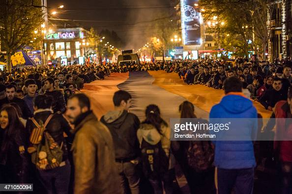 People participate in a torchlight procession carrying a large Armenian flag through the city to commemorate the anniversary of the Armenian genocide...