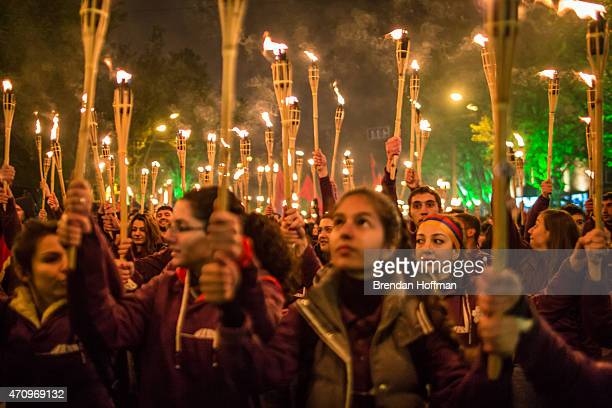 People participate in a torchlight procession through the city to commemorate the anniversary of the Armenian genocide on April 24 2015 in Yerevan...