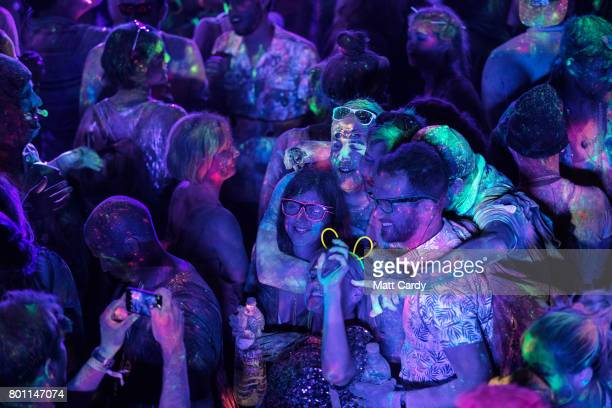 People participate in a UV paint fight at a late night venue at the Glastonbury Festival site at Worthy Farm in Pilton on June 26 2017 near...