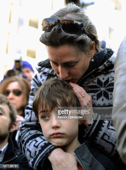 People participate in an interfaith memorial service with members of six churches at a makeshift memorial for victims near the site of the Boston...