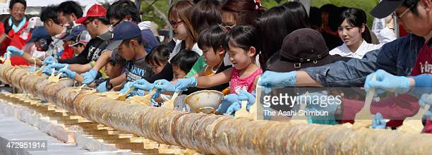 People participate in making the longest baumkuchen cake on May 10 2015 in Chikuzen Fukuoka Japan This was an attempt to create a baumkuchen to...