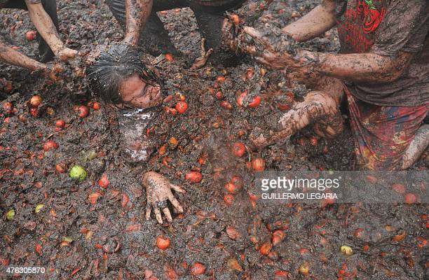 People participate in the ninth annual tomato fight festival known as 'tomatina' in Sutamarchan Boyaca department Colombia on June 7 2015 AFP...