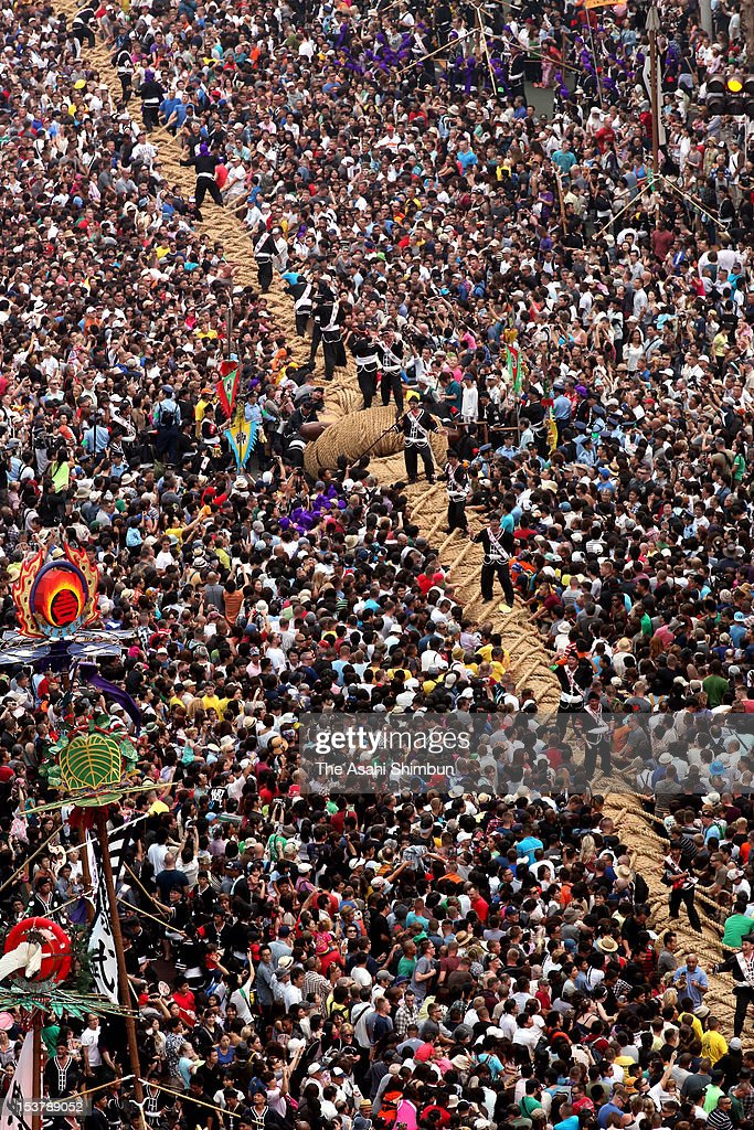 people participate the annual 'Naha giant tug-of-war' at the national road No. 58, high street in Naha City on October 7, 2012 in Naha, Okinawa, Japan. 15,000 people pull a 200-meter rope weighing 43 tons.