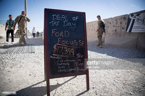 People pass a blackboard advertising a car for sale outside the PX store at Kandahar airfield on November 13 2014 in Kandahar Afghanistan Now that...