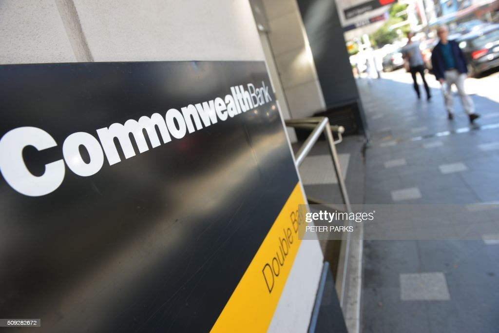 People pass a Commonwealth Bank branch in Sydney on February 10, 2016. Australia's biggest company Commonwealth Bank posted a modest two percent rise in first-half net profit to 3.26 billion USD with the lender confident it is well placed to ride out global instability. AFP PHOTO / Peter PARKS / AFP / PETER PARKS