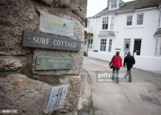 People pass a holiday let property in the town of St Ives which has introduced measures to limit the number of second homes are seen in St Ives on...