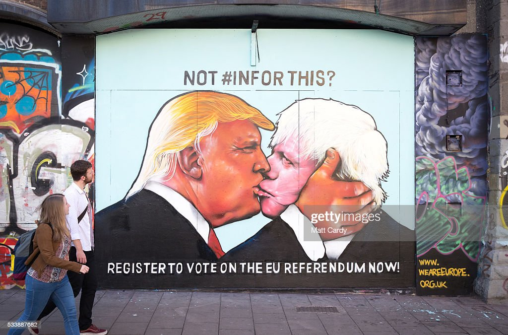 People pass a mural that has been painted on a derelict building in Stokes Croft showing US presidential hopeful Donald Trump sharing a kiss with former London Mayor Boris Johnson on May 24, 2016 in Bristol, England. Boris Johnson is currently one of the biggest names leading the campaign for Britain to leave the European Union in the referendum which takes place on June 23 and Republican presidential hopeful Donald Trump has also backed a so-called Brexit.
