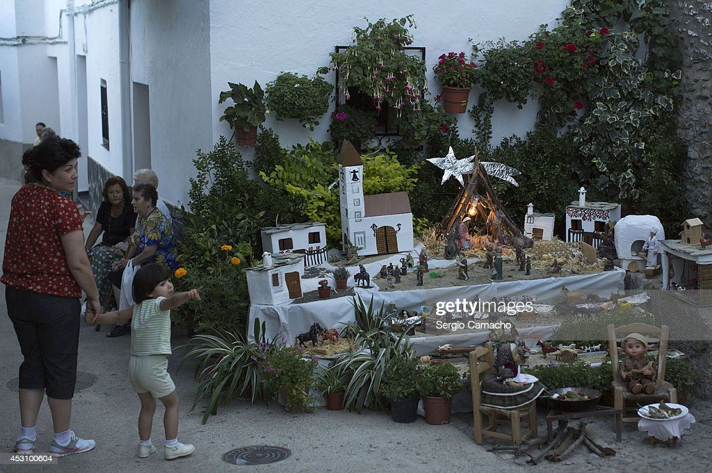 People pass a nativity scene during the New Year's Eve in August celebrations on August 2, 2014 in Berchules, Spain. The town of Berchules, located in Granada, on the southern slope of the Sierra Nevada Mountain Range, has had a curious New Year's Eve tradition in place since 1994. The town experienced a power outage on New Year's eve in 1994 and residents were unable to hold the traditional celebrations, so they decided to move their celebrations to the mid-point of the year, holding them in August instead.