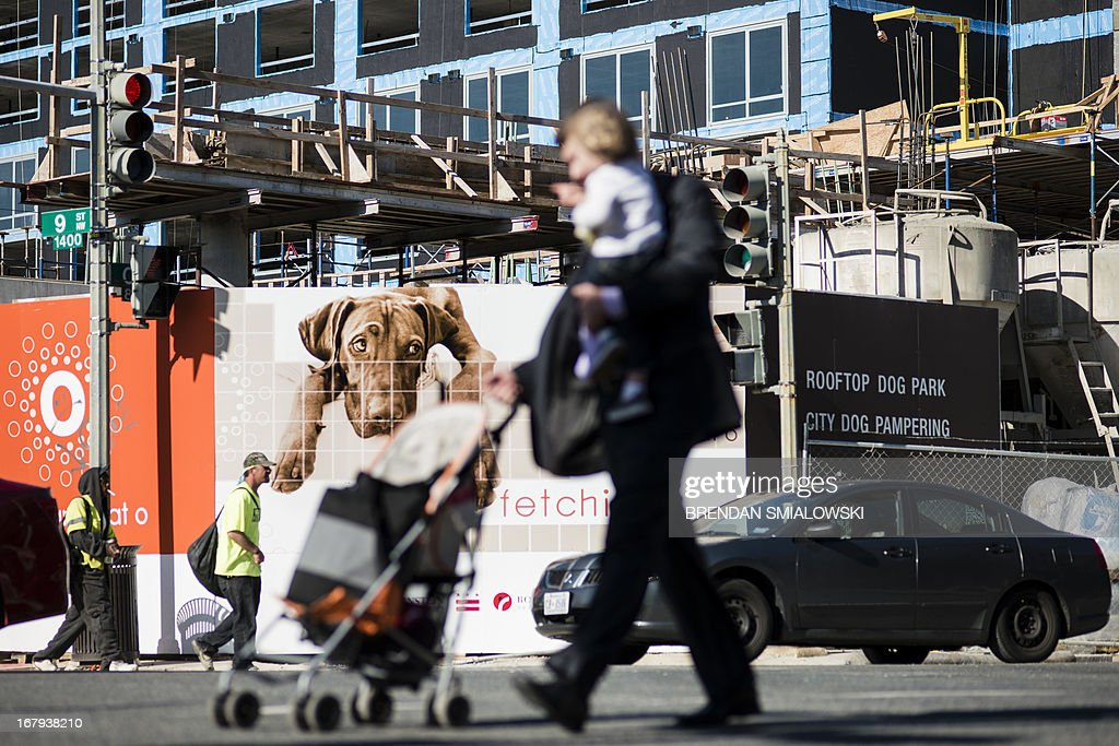 People pass a residential construction site with an advertisement of pet friendly condominiums May 2, 2013 in Washington, DC. AFP PHOTO/Brendan SMIALOWSKI