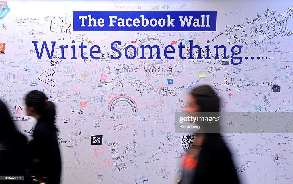 People pass a scribble board wall at the headquarters of Facebook Inc. in Palo Alto, California, U.S., on Wednesday, Aug. 18, 2010. Facebook Inc. unveiled a service that makes it easier for users to share their whereabouts with other people, making a deeper push into a fast-growing market pioneered by Foursquare Labs Inc. Photographer: Noah Berger/Bloomberg via Getty Images