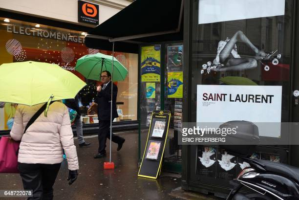 People pass an advertisement for the French luxury fashion brand Yves Saint Laurent on March 6 2017 on the Champs Elysees in Paris A new publicity...