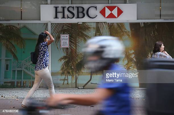 People pass an HSBC branch on June 9 2015 in Rio de Janeiro Brazil HSBC plans to eliminate 50000 jobs from its global workforce while selling off its...