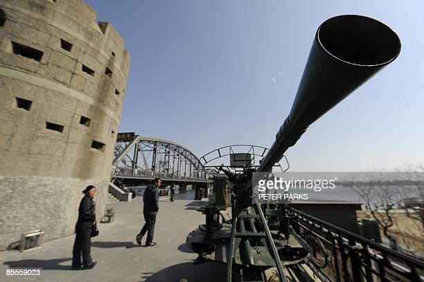 People pass an old antiaircraft gun on a visit to 'Broken Bridge' in Dandong on March 23 2009 which previoulsy connected China and North Korean...