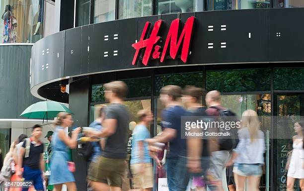 People pass by a branch of HM department store on August 14 2015 in Frankfurt Germany
