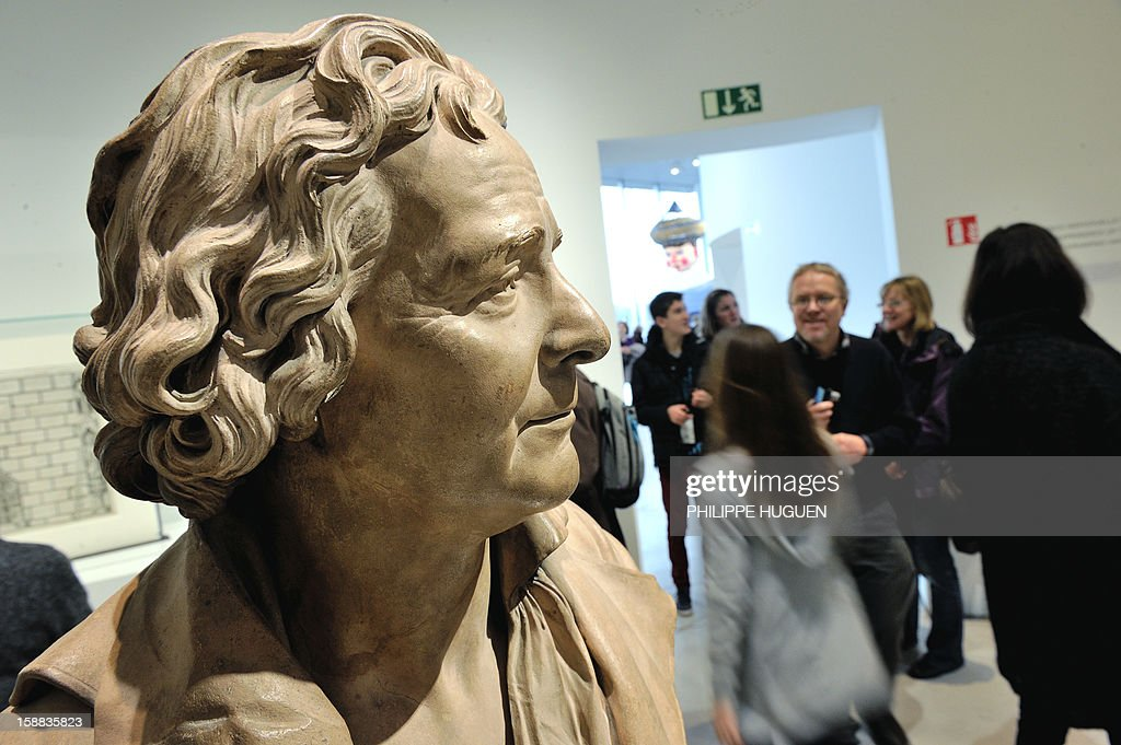 People pass by a bust of French sculptor Augustin Pajou at the Louvre-Lens museum on December 31, 2012 in Lens, northern France. Three weeks after its inauguration, the museum welcomed its 100.000th visitor on December 28, 2012. AFP PHOTO PHILIPPE HUGUEN
