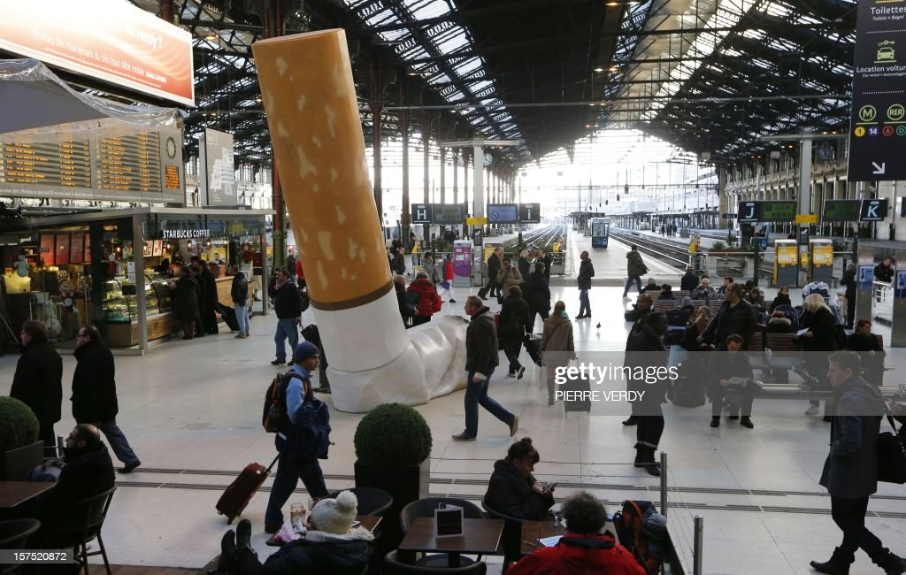 People pass by a giant mock-up discarded cigarette displayed on the ground at the Gare de Lyon railway station in Paris, on December 4, 2012, as part of a public-awareness campaign launched by France's national rail company SNCF to shed light on commuters' disrespectful behaviour.