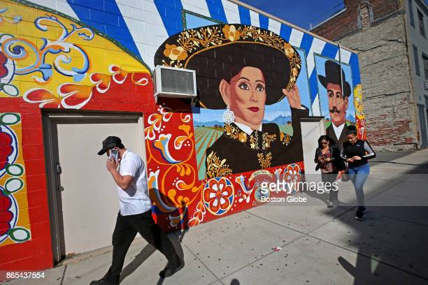 People pass by a mural that is part of the #ToImmigrantsWithLove campaign on Paris Street in East Boston on Oct 19 2017 A host of efforts honoring...